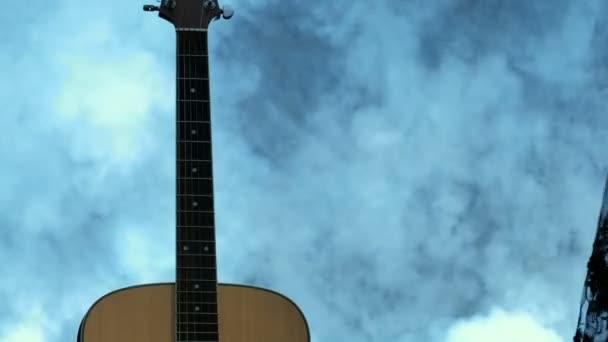 Dívka ve večerních šatech se blíží akustickou kytaru a vede ruku podél řetězce zdola. Kouř na pozadí. Den hudby.