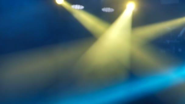 Blikající modré a žluté světlo v kouři na koncert rockové scéně. Rozmazané pozadí záběrů.