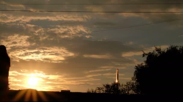 Život ve městě při západu slunce. Siluety chodců, cyklistů a vozidel