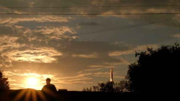 Kazachstán. Léto roku 2018. Život ve městě při západu slunce. Siluety. Lidé přes silnici na přechodu pro chodce, budou projíždět auta. Chlap na kole na chodníku
