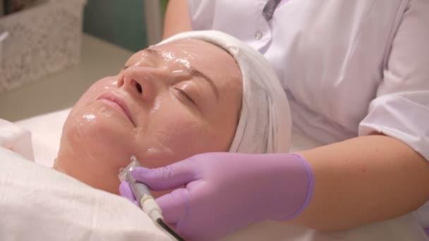 Una donna di mezza età sulla procedura in un salone di bellezza. Sollevamento, tono della pelle. Un cosmetologo professionale leviga le rughe sulla guancia della ragazza con laiuto di due elettrodi. Terapia a microcorrente