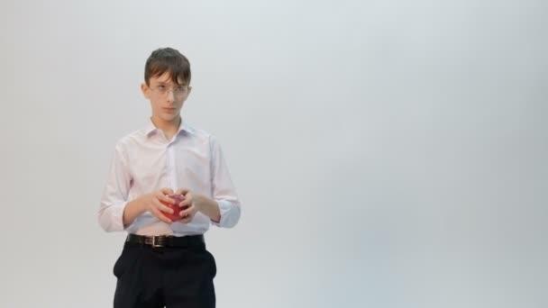 Ein junger Mann ist Student oder Schüler mit Brille und weißem Hemd mit einem roten Apfel in der Hand. Teenager macht lustige Tanzbewegungen mit ihren Hüften. Emotionen. Vereinzelt. Freiraum. Unbearbeitetes Video.