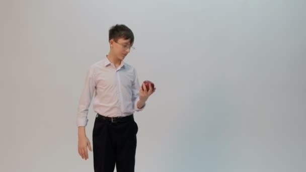 A funny-looking teenager shows hands with emotions of indifference and not knowledge. A student or a schoolboy with glasses and a white shirt with a red apple in his hand. Isolated. Free space.