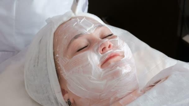 Die Nahaufnahme der Hände einer professionellen Kosmetikerin in weißen Handschuhen legt eine pflegende Creme mit einem Pinsel auf das weibliche Gesicht. Frau lächelt bei Hautverjüngung im Schönheitssalon.