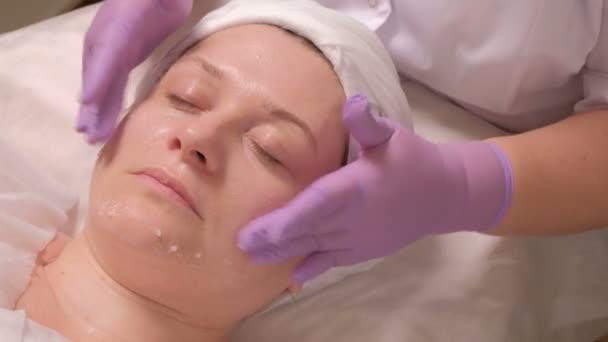 A női arc a szépség szalonban kozmetikai eljárás. A bőr fiatalító hatását. Közelről. A kezében egy kozmetikus, a kesztyű tesz egy tápláló gél magában egy középkorú nő.