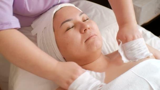 kosmetischer Eingriff. Nahaufnahme einer orientalischen Frau. Die Hände der Kosmetikerin wischen Gesicht und Hals des asiatischen Mädchens mit feuchten Tüchern ab. Verjüngend und entspannend.