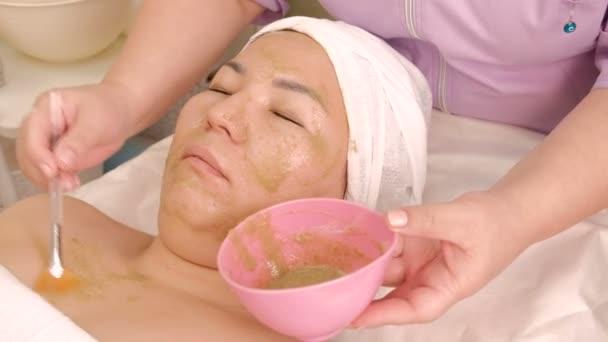 Kozmetikai eljárás alkalmazása ázsiai nő anti-aging alga maszk. Egy profi kozmetikus kiterjed a lány s arc és a nyak zöld keverékével egy kozmetikai kefe segítségével. Egészség és szépség.