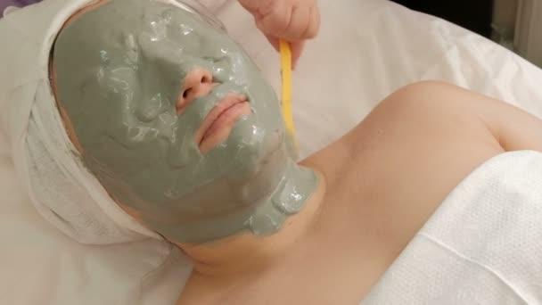 Das Auftragen einer Alginatmaske auf den weiblichen Hals in einem Schönheitssalon. kosmetische Verfahren für Frauen. Moderne Kosmetologie zur Verjüngung und Reinigung der Haut.