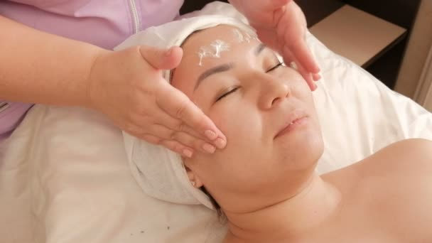 A beautician applies white cream to the face of a middle-aged Asian woman in a beauty salon. Rejuvenation, relaxation and healing of the skin. Cosmetic procedure for girls.