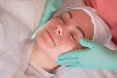 The girl goes through facial treatments in the beauty salon. Beautician wearing gloves apply moisturizer on the woman's face. Facials at the Spa