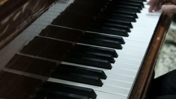 A srác zongorázik. Kezében egy fiatal férfi nyomja meg a fehér és fekete gombok egy hangszer. Egy koncertre próbája egy fiatal zongorista.