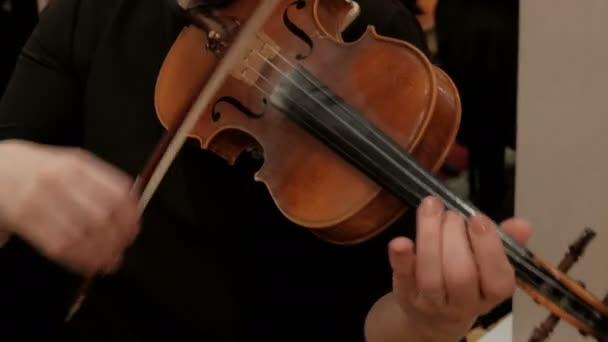 A nő befejezi a hegedű és eltávolítja a hangszer a vállát. Jobb női kéz egy gyűrűvel az ujját. Közeli-megjelöl-ból egy szeretetre méltó női hegedűművész kezek.