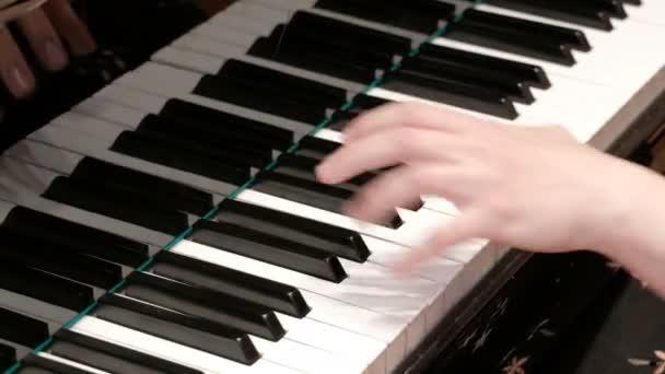 Zongorázni. Közeli. Zenei téma. Koncert program. Női kezek sajtó zongora billentyűk.