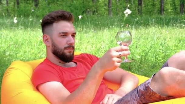 Ten chlap leží na nafuatelné matraci na zelené trávě v lese. Sklenice s vínem v ruce. Bruneta s plnovousem odpočívá a pije víno na pikniku. Pojetí požitků a životního stylu.