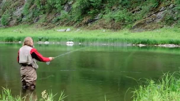 Egy középkorú férfi egy szakállas és hosszú haja legyező horgászat egy hegyi folyón. Egy vízálló öltönyt Halász áll a vízben egy horgászbot a kezében. Sport és hobbi.