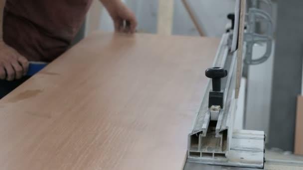 A munkás egy olyan gépen helyez el forgólapot, amelynek körfűrészelésénél a fűrészeléshez korlátozó limiter van. Famegmunkálás műhely. Az átlagterv. Bútorkészítés.