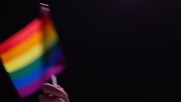 Mužská ruka mává duhovou vlajku. Symbol svobody a lásky lidí stejného pohlaví. Pojetí sexuálních menšin. Vlajka pýchy na černém pozadí