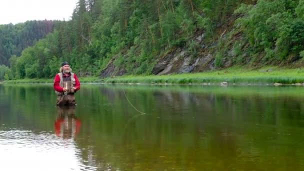 Egy idős férfi piros ruhában és kendővel a fején horgászfelszerelést dob. Horgászni a folyón a hegyekben. Sport vagy hobbi. Átfogó terv. Népszerű nyaralóhely.