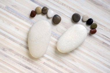 Two tiny stone feet and ten toes on wooden background, stone in the shape of a human feet