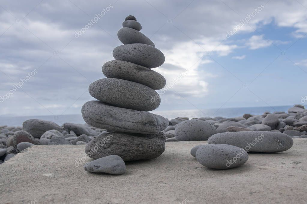 Stone cairn tower, poise stones, rock zen sculpture, light grey pebbles