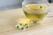 Matricaria chamomilla flowers and trasparent cup of tea on wooden table, fresh flowering herbal medicine in glass mug