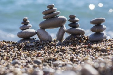 Stones and pebbles stack, harmony and balance, three stone cairns on seacoast with ocean waves on background