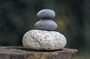 Three zen stones pile on wooden stump, white and grey meditation pebbles tower