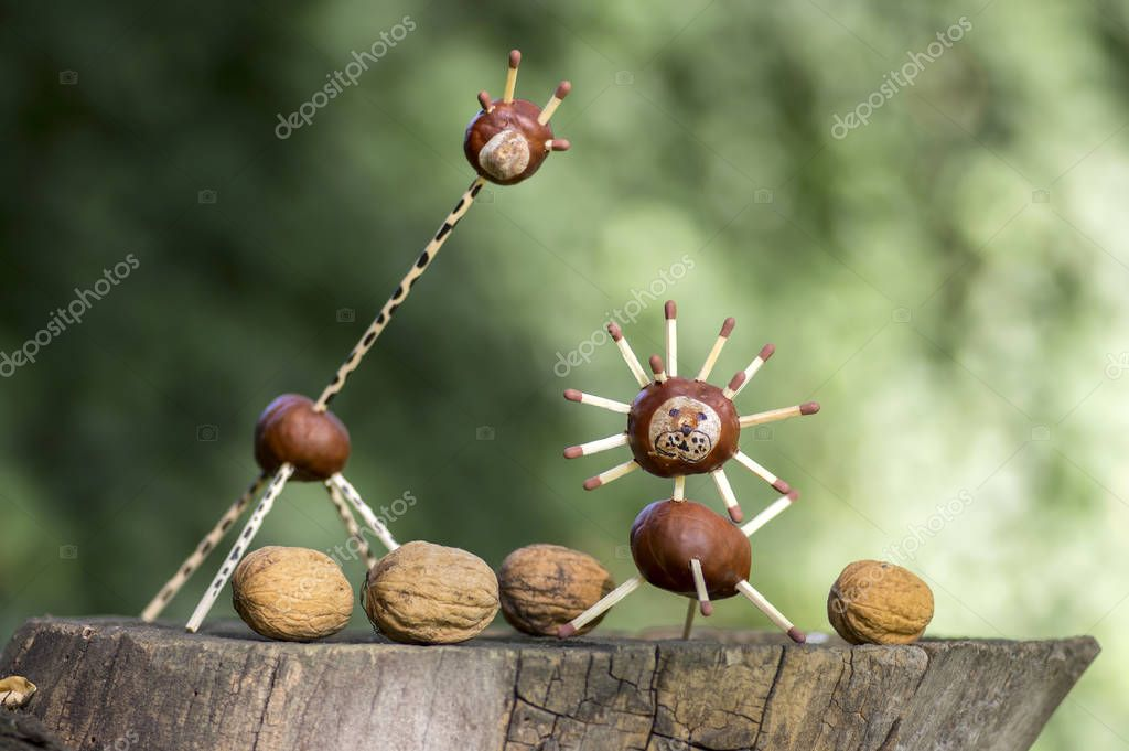 Two funny chestnut animals on tree stump, green background, traditional autumn handcraft, lion and giraffe