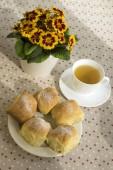 Domácí tradiční české buchty plněné povidly, rozinek a tvaroh na bílém štítku na stůl s čajem a květi