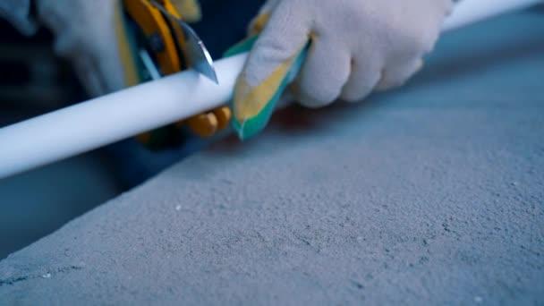 Instalatérské rukavice řežou PVC trubku nůžkami. Detailní záběr rukou v rukavicích.