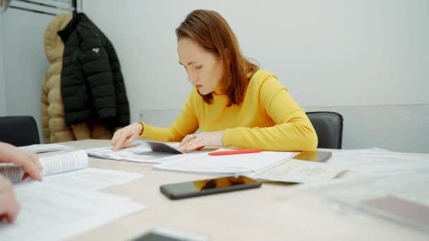 Žena na recepci v kanceláři ověřuje údaje o pasech ve smlouvě..