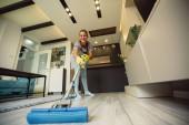 Mladá žena v ochranné rukavice čištění podlahy s mopem