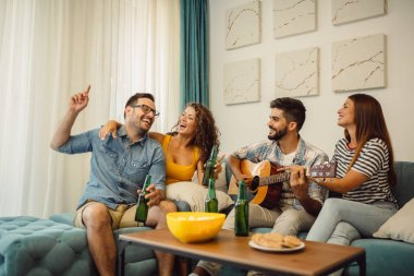 Group of young friends having fun with guitar, drinking beer and eating popcorn indoors