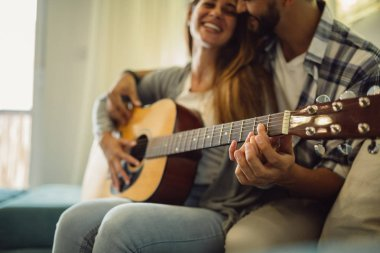 Close shot of young bearded man who teaches his girlfriend to play guitar.