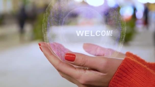 weibliche Hände mit Hologramm mit Willkommenstext
