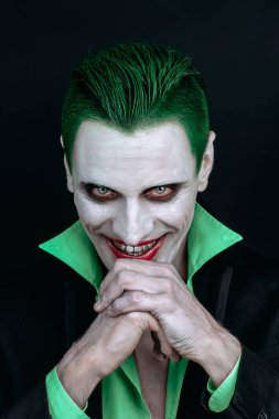 Portrait of a joker. Makeup for Halloween. Crazy image of a man in a green shirt with green hair