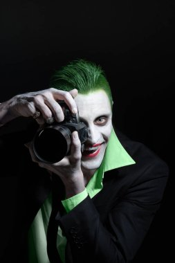 Portrait of a joker. Makeup for Halloween. Crazy image of a photographer man in a green shirt with green hair with camera in hand