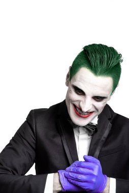 Portrait of a joker. Makeup for Halloween. Crazy image of a man in a black suit and a white shirt with a butterfly. green hair