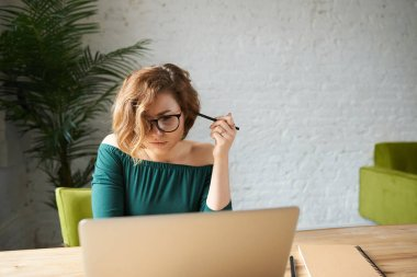 Attractive young female freelancer in glasses and dress sitting at table at home office, working remotely on laptop.