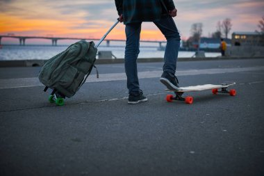 Man start new trip from home city. Extreme concept with male longboarder stay with suitcase before adventure in summer time. Travel and tourism style.