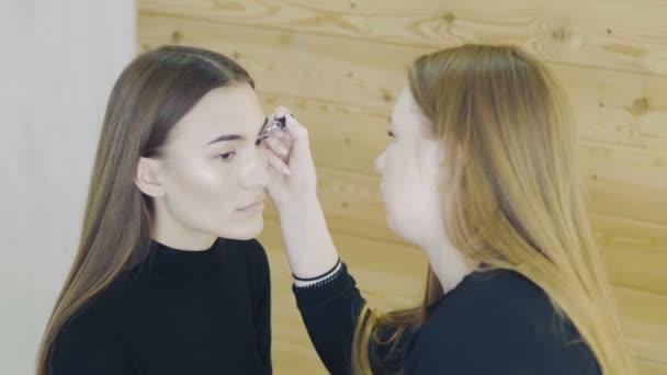 Oční make-up žena použití eyeshadow prášek. Oči Makeup.Make-up.Eyes stíny. Oční stíny kartáč. Vizážistka dělá make-up očí mladé ženy. Vizážista štětcem na obličej dělá