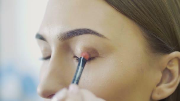 Oční make-up žena použití eyeshadow prášek. Krásná žena tvář. Dokonalý make-up. Módní krása. Řasy. Kosmetické oční stíny. zblízka. Zpomalený pohyb