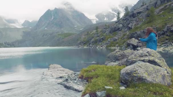 Altai, Kucherla, RUSSIA: Girl against a blue lake and mountains. The girl is spinning. Hands up. 4k Slow motion