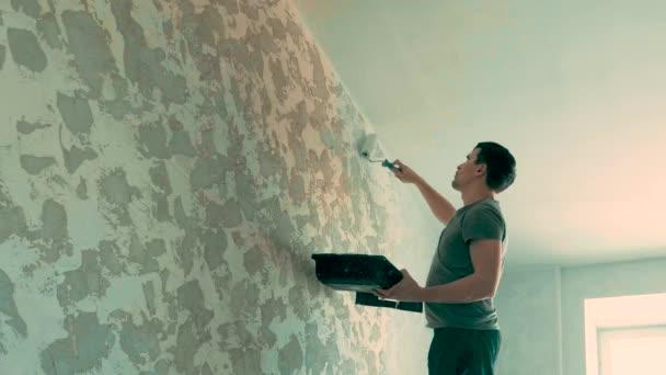 Zadní pohled na zdi obraz malíře s válečkem. Zadní pohled na malíře v bílé montérky, helma a rukavice jednu stěnu s válečkem. zadní pohled na mladíka malíř v malířství pracovní oděvy