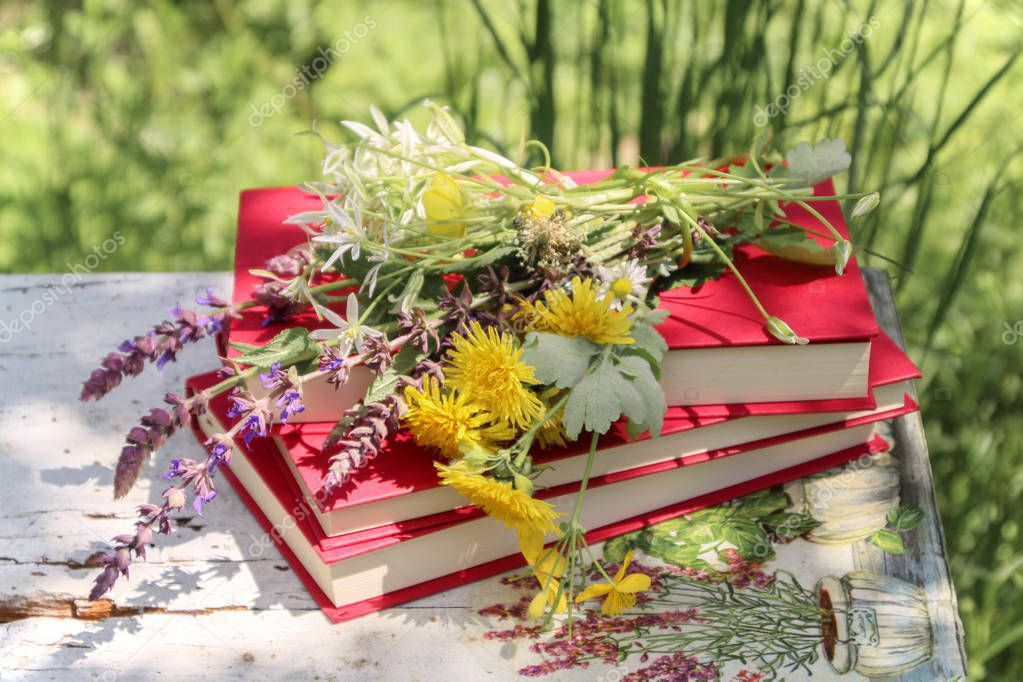 Still life in a rural garden with books and wild flowers on a vintage table