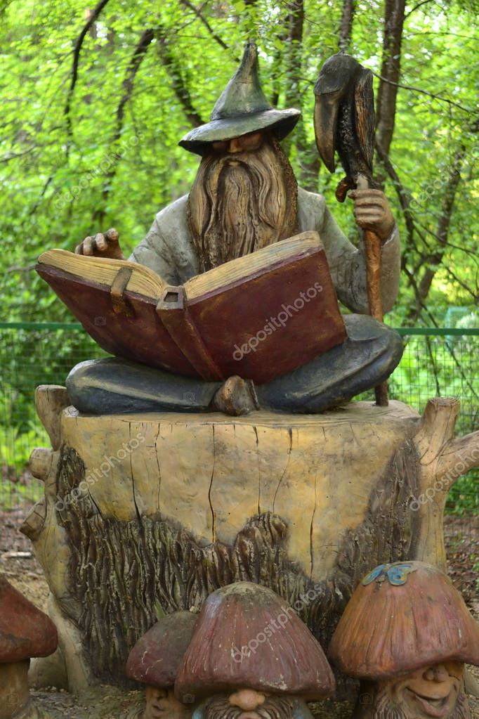 Simple still-life photo of wooden wizard with book in the forest