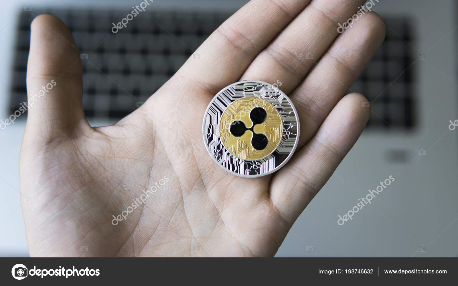 Ripple coin on a laptop keyboard closeup on a miner hand