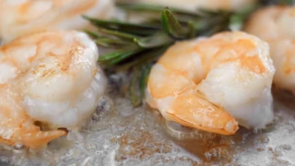 Close up on a shrimps fry on a frying pan with a garlic and rosemary.