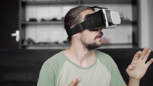 Young bearded hipster man using his VR headset display for virtual reality game or watching the 360 video and trying to touch to something he see while sitting on sofa. VR Technology.