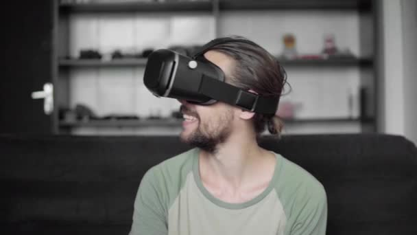 Young bearded hipster man start using his VR headset display with headphones for virtual reality game or watching the 360 video and captivated and surprised by something.